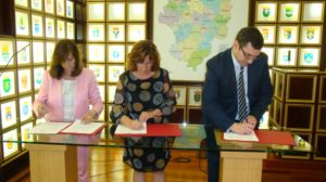 La presidenta de la FAMCP, Carmen Sánchez, la consejera de Ciudadanía y Derechos Sociales, María Victoria Broto, y el director general de Multienergía Verde, Francisco Cruz, firmando el convenio.