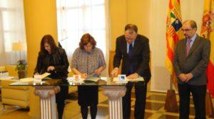 La presidenta de la FAMCP, Carmen Sánchez, la consejera de Ciudadanía y Derechos Sociales, Mª Victoria Broto, y el director general de Endesa-Aragón, Ignacio Blanco, firman el convenio en presencia del presidente del Gobierno de Aragón, Javier Lambán.