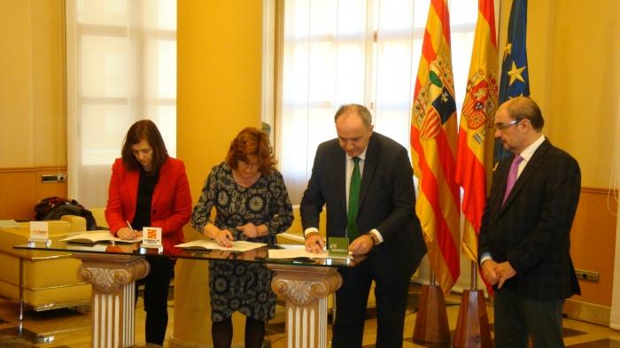 Desde la izquierda, Carmen Sánchez, Mª Victoria Broto y Eduardo Insunza firman el convenio en presencia de Javier Lambán.